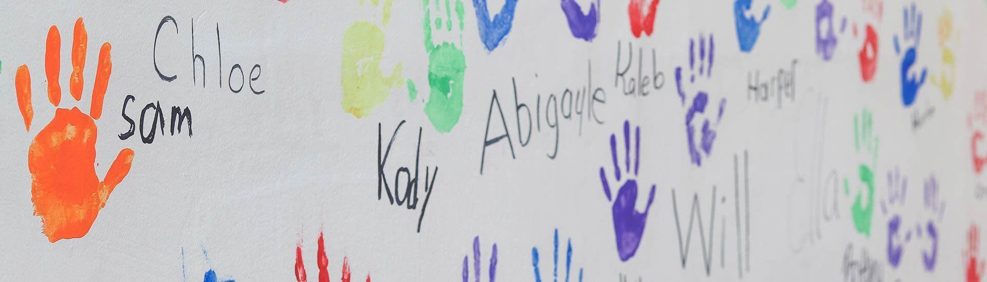Wall with handprints of program graduates
